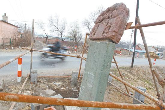 昨日,沈阳市于洪区马三家子镇永安桥旁,地上仍有车体的残片和一摊油污,被吉普车撞到的石碑被铁架包围起来,碑上半部仍摇摇欲坠。