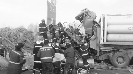 消防人员使用液压设备强行扩张开驾驶室残骸,将受伤司机解救出来。摄影杨德欢