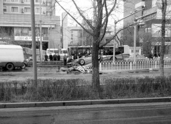 """昨日早5时35分,一辆灰色大众轿车由沈河区万柳塘路右转至文化路方向时,撞弯护栏20余米后,""""仰""""在路中央,所幸女司机没有受伤。读者供图"""