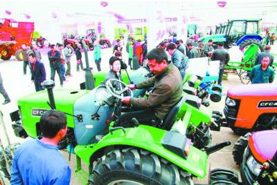 参加现代农机装备展示交易会的农民选购拖拉机