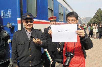 """小伙在一张纸上写了""""别了,6331""""引起列车工作人员兴趣,也拍照一张留作纪念。"""