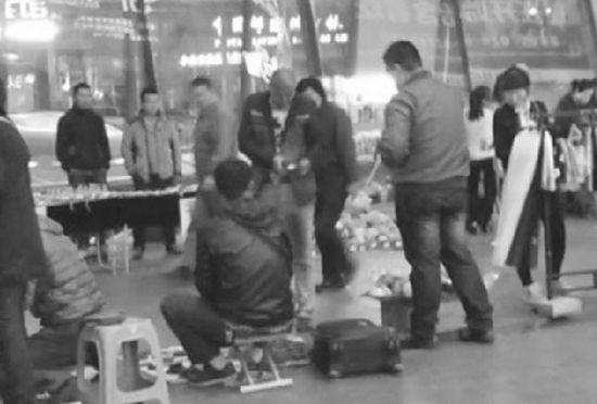 百联购物中心南侧广场上,记者刚刚把袜子摊摆放好,一名光头男子就开始收钱。