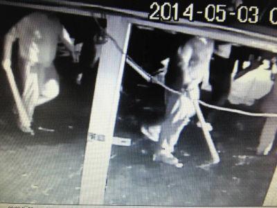 手持棍棒的男子被监控录下身影。