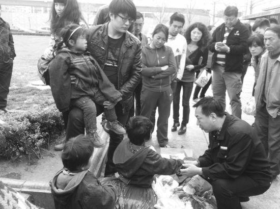 救助人员在街头劝说乞讨的祖孙四人去救助站。