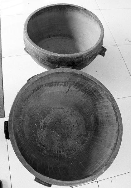 """张树忠及其老伴李桂贤挖出来的这两个铜锅是辽代铜器文物,距今已有1000余年历史,是行军用的炊具""""六耳铜锅""""。"""