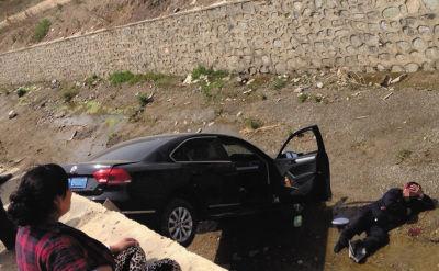 黑色轿车掉进沟内,一个男子躺在沟内,头部流血。