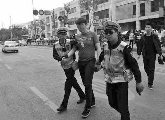 昨日下午3时许,沈阳市皇姑区长江街崇山路交通岗,年轻小伙从设卡检查的警察手中一把拽回自己的摩托车,骑上就跑,却撞倒人行道上9岁小女孩。随后小伙被警方带走调查。本组图片由读者供图
