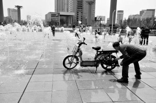 男子在喷泉广场上刷车。