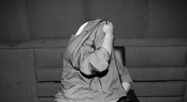 昨晚,在沈阳市公安局交警支队北站大队,一名无证驾驶的司机在镜头前用衣服遮住脸。   北国网、辽沈晚报记者 查金辉 摄