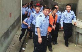 5月20日,新化县,犯罪嫌疑人伍涛在公安民警的看押下指认现场。