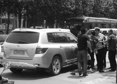 """穿着""""军胜驾校""""字样T恤的几个人与黄色货车司机打在了一起,交警正在拉开他们。"""