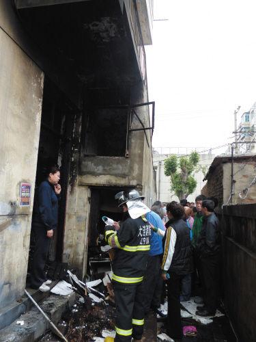 仓库发生爆炸引起火灾,消防队员正在现场勘查。