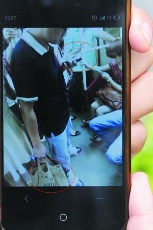 男子左手拿着显示器,右手袋子里藏着针孔摄像机。