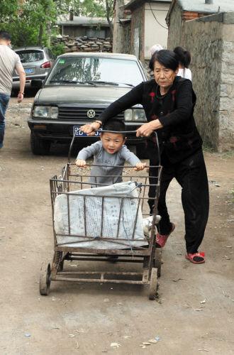懂事的宝宝在帮外婆推垃圾车。