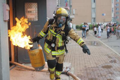 消防队员徒手抢出燃烧的液化气罐。(警方提供)