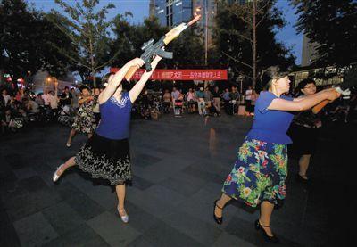 """昨晚,北京东直门来福士广场,一群中老年广场舞爱好者表演""""杀鬼子""""广场舞,不少市民前来围观。"""