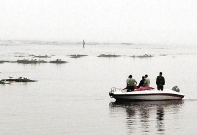 救生快艇正在慢慢接近被困男子(画圈处)。
