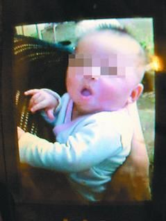男童外公出示手机上他四个月大的照片,长的白胖可爱。