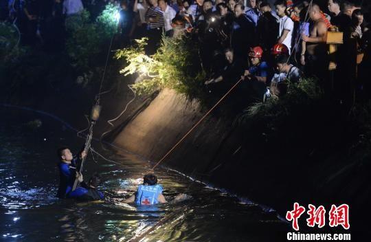 三位打捞人员正在将绳索捆绑于起重机上,以此拉出事故车辆。 杨华峰摄