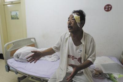 店主在医院向记者讲述事情经过。
