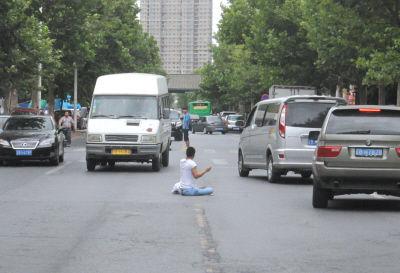 """男子坐在马路上""""指挥交通""""。 右上方小图:手按井盖做出奇怪动作。"""