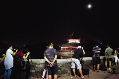 昨晚,摄影爱好者在故宫角楼下拍月亮。新京报记者 高玮 摄