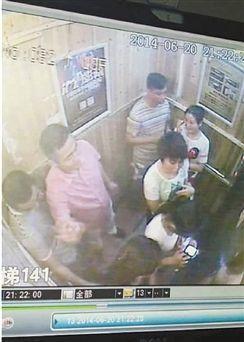 粉衣男子对着电梯门挥手。