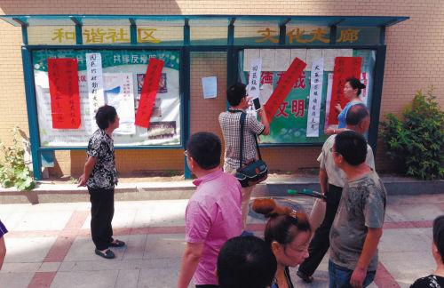 万众家园内的文化展板上贴着一些红白两色的纸条,引得进进出出的人们议论纷纷