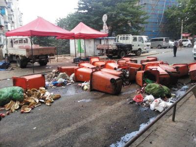 十多个垃圾桶倒在马路上,垃圾撒得到处都是
