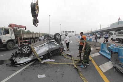 轿车翻扣在马路上,车损严重