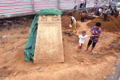 发掘出的墓碑吸引了不少围观群众,不远处文研所人员正在挖掘两处棺木。