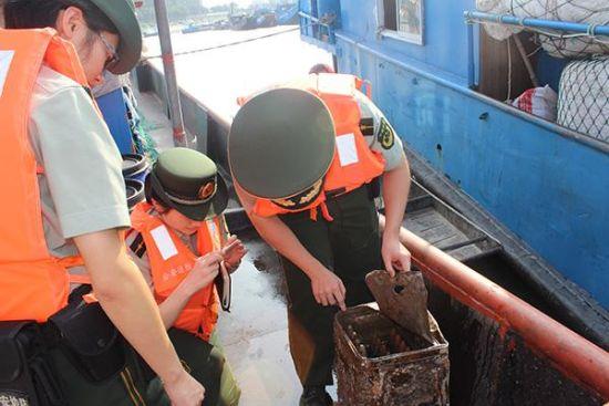 上海市三甲港边防派出所的民警正在对打捞上来的炮弹进行初步勘查。 陆泽昭 图