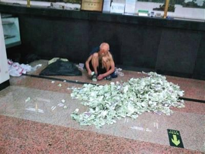 中秋节后,乞讨老人蹲在邮局大厅内清点成堆的零钞。据知情者称,老人月均汇款万元左右。 网友供图