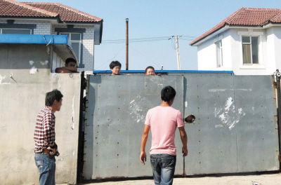 工人们紧闭大门守着厂子。