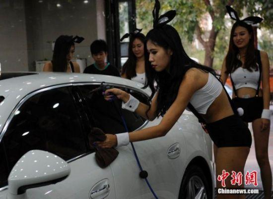 图为比基尼兔女郎在清洁一辆豪车。