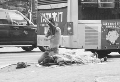 一人躺路边一人乞讨