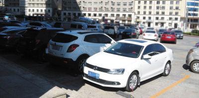 广场上画了车位,不少车辆停在这里。
