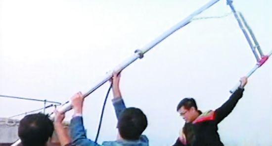 8日,抚顺市一小区32楼天台上,抚顺市无线电管理委员会的工作人员正在拆卸非法广播电台的天线。
