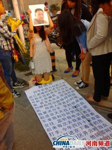 女孩双膝跪地地上放着举报材料。中国日报网