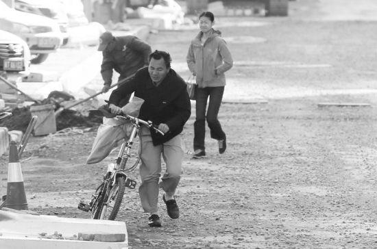 风中,自行车骑不动了,只能推着走。半岛晨报、海力网摄影记者张腾飞