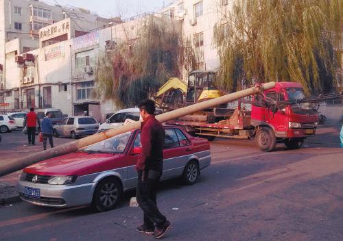 被剐倒的线缆杆砸扁路边出租车
