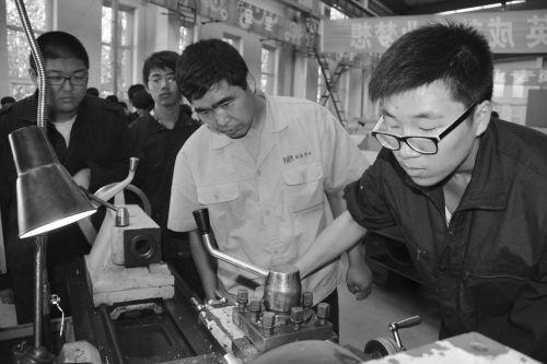 图为肖友才(右二)指导学生。