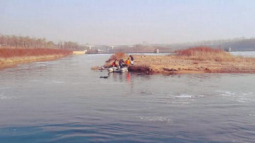 小岛四周水流湍急,俩人忙求助 消防出动冲锋舟,成功实施救援。
