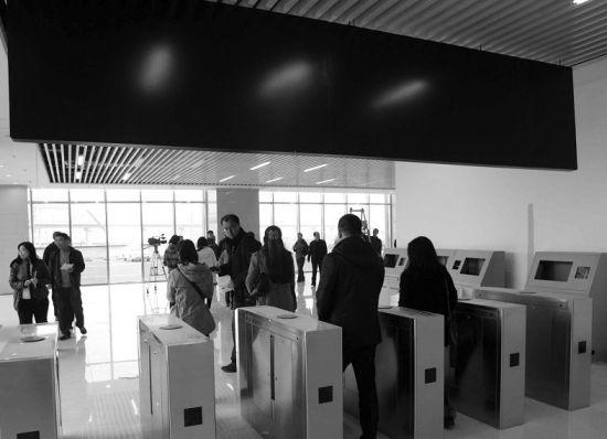 旅客通过崭新的检票机上车