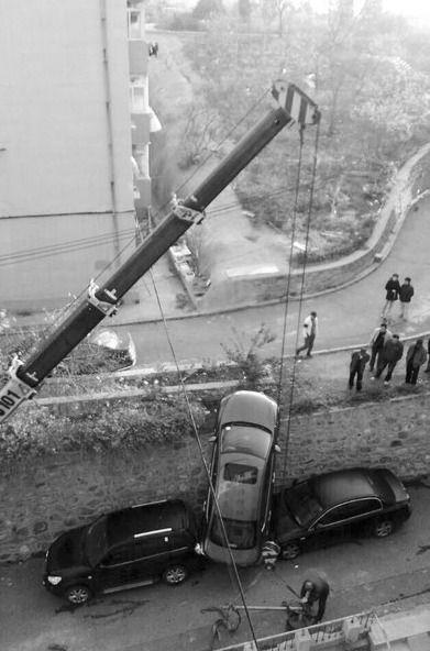 新手倒车栽下3米高墙,将下面两车砸伤。半岛晨报、海力网摄影记者孙振芳