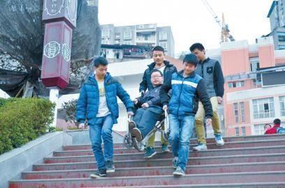 学生们用轮椅轮班接送邱民。