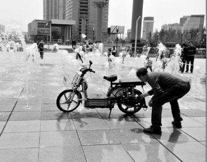 男子借喷泉水刷车